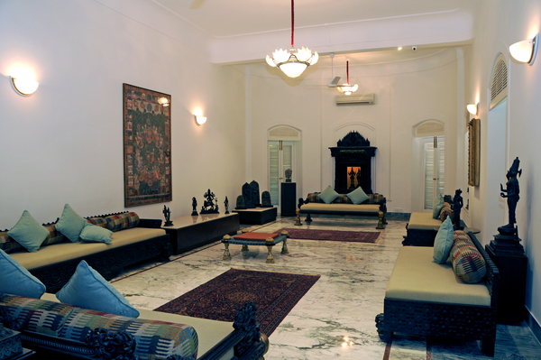 The living room has bronzes, stone sculptures and a pichvai painting